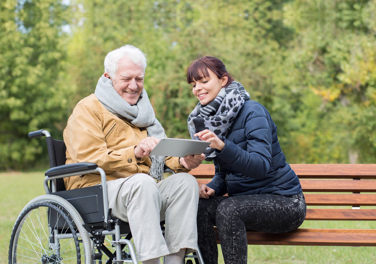 caregiver helping the patient with his tablet
