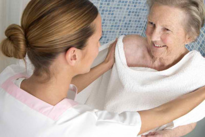 caregiver assisting a senior woman in taking a bath