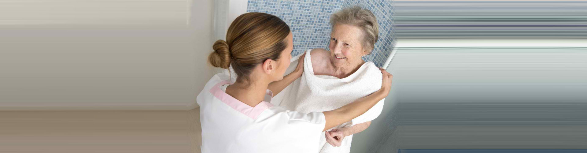 caregiver assisting senior woman in taking a bath
